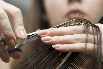 Close-up of hairdressers hands cutting long hair